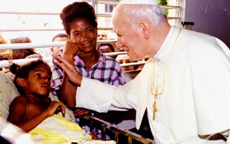 Papa Giovanni Paolo II benedice un bambino durante una visita a un ospedale pediatrico il 13 ottobre 1992 a Santo Domingo (foto: Getty Images)