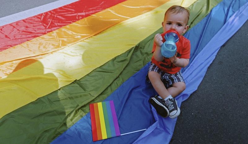 Foto: un bambino beve acqua durante il gay pride in Bucharest (Bogdan Cristel/Reuters)