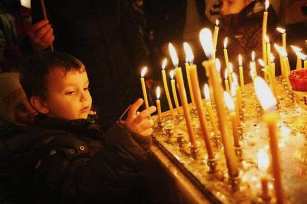 Un bambino accende una candela durante la messa di Natale (haak78, Shutterstock)