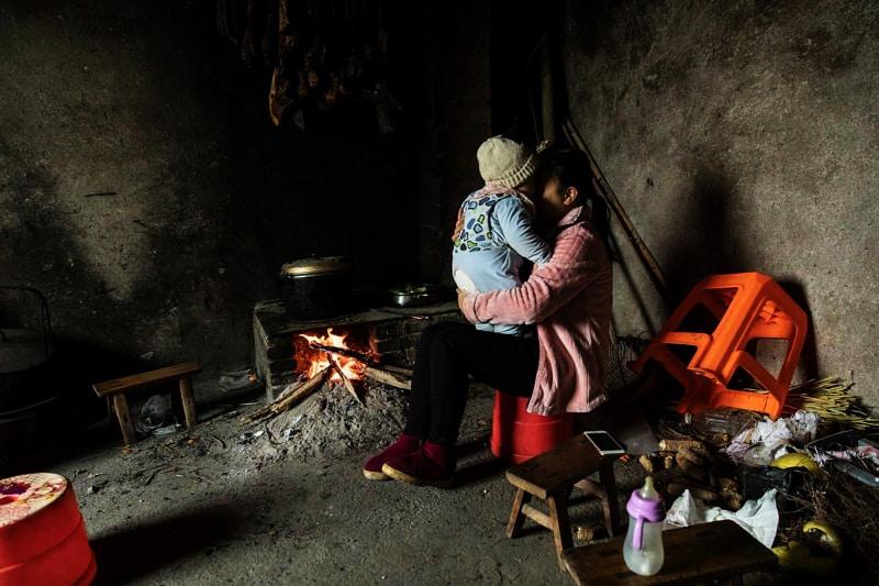 Xie Xianmei tiene suo figlio accanto al caminetto nella casa della sua famiglia adottiva a Bailie township, Dazhou, Cina. PHOTOGRAPHER: QILAI SHEN/BLOOMBERG