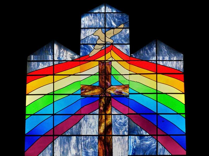 Vetrata con il simbolo arcobaleno in una chiesa