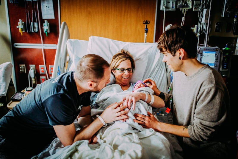 In questa foto del 25 marzo 2019, Matthew Eledge, a sinistra, sua madre Cecile Eledge, al centro, e il marito di Matthew, Elliot Dougherty, a destra, saluta la piccola Uma dopo il parto al Nebraska Medical Center di Omaha, Neb. (Ariel Panowicz via AP)
