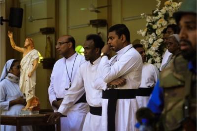 Suore, ecclesiastici e funzionari di polizia guardano la scena dopo un bombardamento alla chiesa di San Sebastian a Negombo, Sri Lanka, 21 aprile 2019. (Foto del CNS / Reuters)