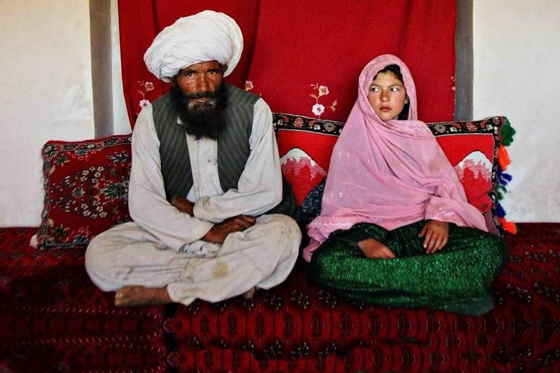 Sposa Bambina - Faiz Mohammed, 40 anni, e Ghulam Haider, 11 anni, si siedono nella sua casa prima del loro matrimonio nel villaggio rurale di Damarda, in Afghanistan, l'11 settembre 2005