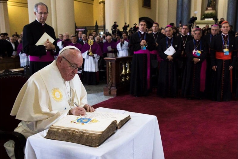 Papa Francesco mentre firma un documento