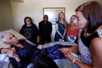 In questa foto del 10 maggio 2019, la volontaria di End of Life Washington, Stephanie Murray, a destra, porta i farmaci che metteranno fine alla vita di Robert Fuller (sinistra) mentre si trova a letto, a Seattle.