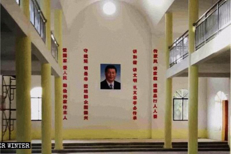Il ritratto del presidente Xi Jinping appeso al centro della parete della chiesa, con slogan di propaganda a entrambi i lati