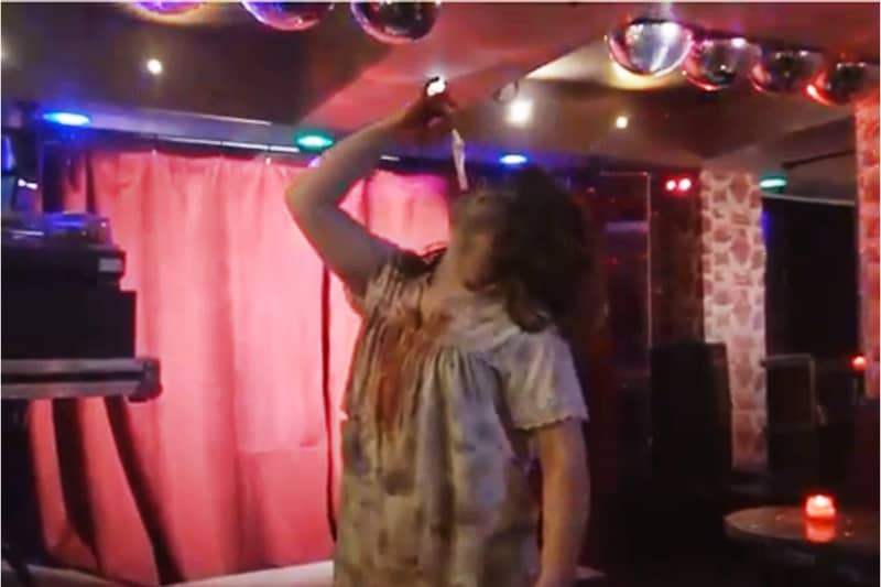 La drag queen Ivy Adamas tira fuori un preservativo dalla bocca durante il suo spettacolo.