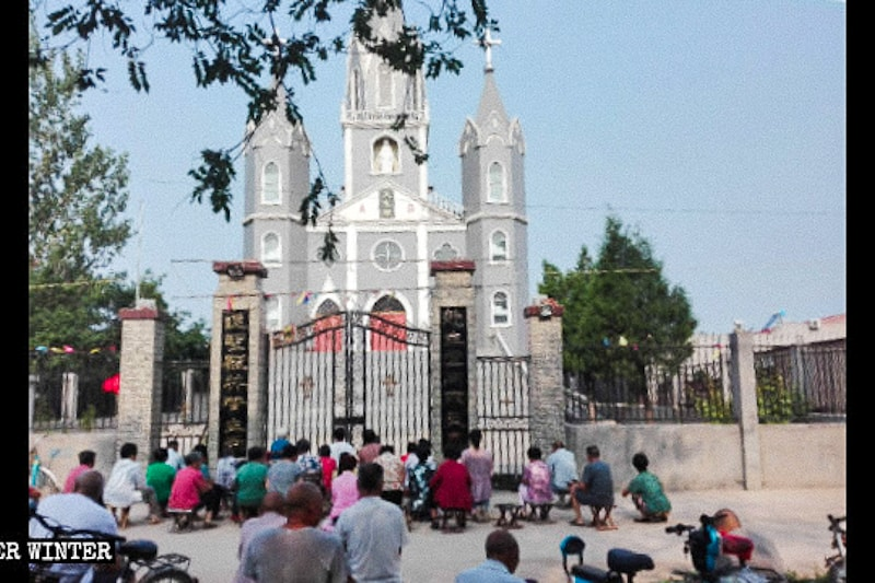 Fedeli cinesi continuano a pregare anche se la loro chiesa è stata chiusa.