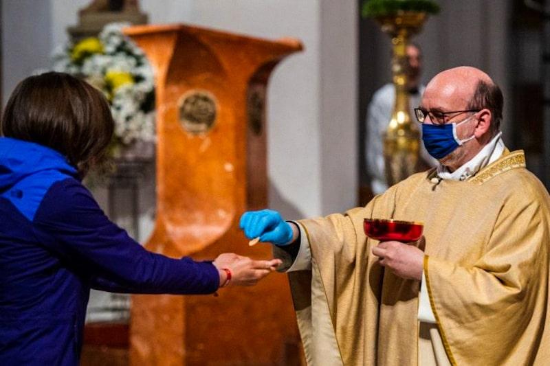Sacerdote distribuisce la Comunione con guanti e mascherina, coronavirus, messa