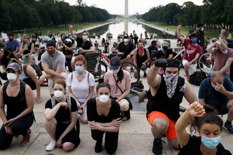 Dimostranti si inginocchiano davanti al Washington Monument durante una protesta contro la morte di George Floyd a Washington, D.C., 4 giugno 2020. (Erin Scott/Reuters)